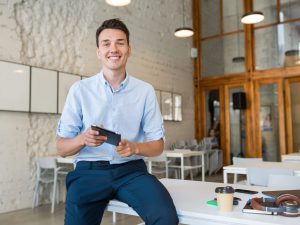 young stylish smiling man in co-working office, startup freelancer holding using tablet, modern office room workplace, student education online